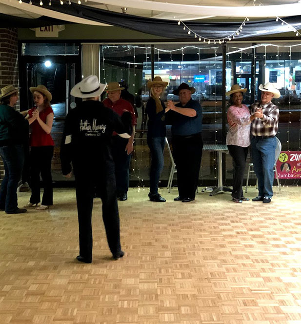 group learning to dance wearing cowboy hats